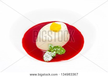 panna cotta in a white plate with raspberry sauce and decorated with pineapple mint