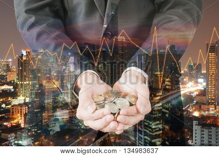Double exposure of cityscape and businessman collect many coins on hands with trading graph finance and banking concept