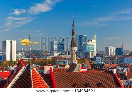 Aerial cityscape with old town hall spire, roofs, golden weather vane and modern office buildings skyscrapers in the background in Tallinn in the day, Estonia