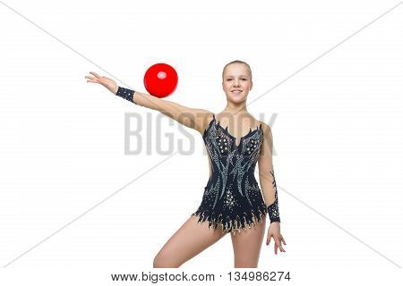 Gymnast girl in beautiful costume making jumping exercise with red ball. Isolated over white background. Copy space.