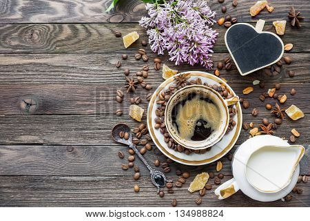 Rustic wooden background with cup of coffee milk sugar ginger and lilac flowers. White vintage dinnerware and spoon. Heart shaped chalk board. Breakfast at summer morning. Top view place for text.