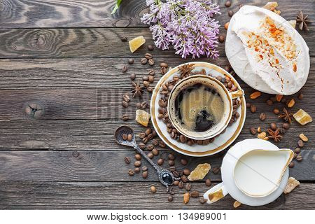 Rustic wooden background with cup of coffee milk meringue with peanuts and lilac flowers. White vintage dinnerware and spoon. Breakfast at summer morning. Top view place for text.