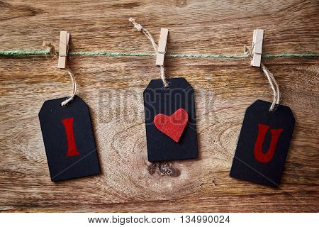 cord, blackboard and clothespins on wood with i love you written