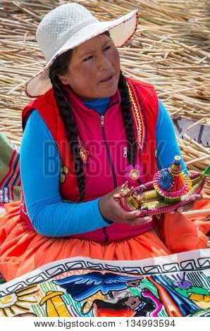 TITICACA PERU MARCH 19 2015: Local women in traditional attire work sell handicrafts to tourists at Uros islands on Titicaca lake in Peru.