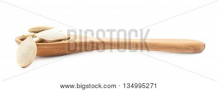 Wooden spoon full of pumpkin seeds isolated over the white background