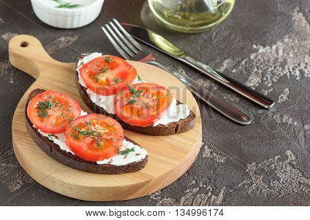 Sandwich with soft cheese and red tomatoes