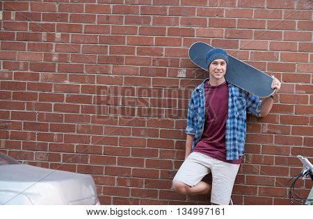 Cool urban skateboarder posing in front of brick wall