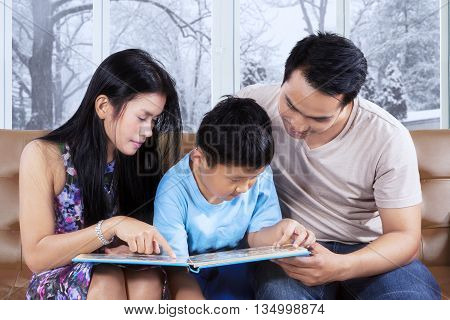 Photo of two happy parents and their son sitting on the sofa while reading storybook with winter background on the window
