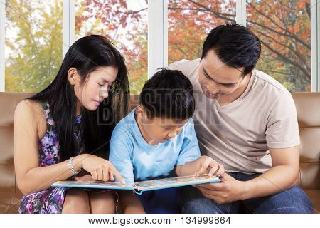 Photo of a cute boy and his parents sitting on the couch while reading a storybook at home with autumn background on the window
