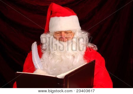 Closeup of Santa Claus writing in his Naughty and Nice Book. Horizontal format with a maroon background.