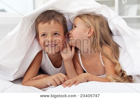 Happy smiling kids sharing their secrets under the quilt