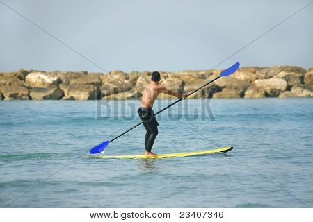 man on paddle board over sea