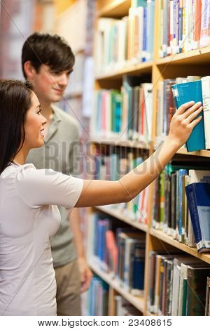 Portrait of students choosing a book on a shelf in a library