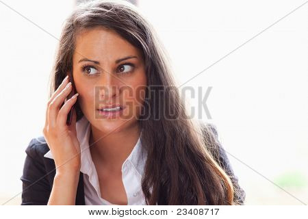 Surprised woman making a phone call while looking away from the camera