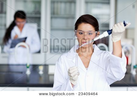 Female scientist pouring a liquid in a tube in a laboratory