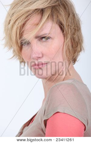 50 years old woman with tousled hair looks anger or in trouble