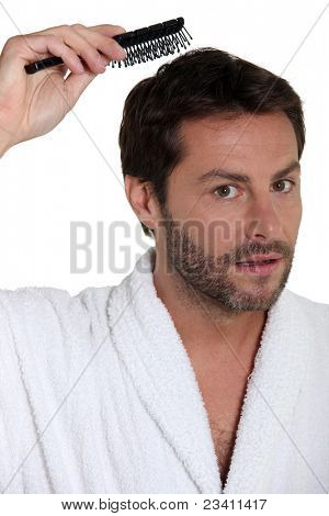 Man in a toweling robe brushing his hair