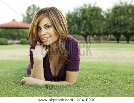 Cute young woman relaxing while lying on the grass in a park.