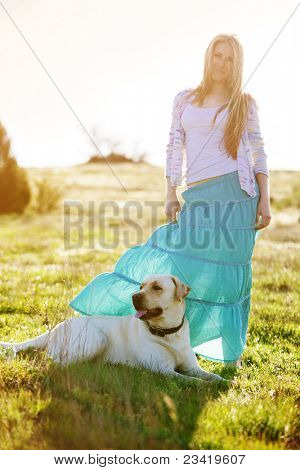 Young woman with ger dog resting at green field