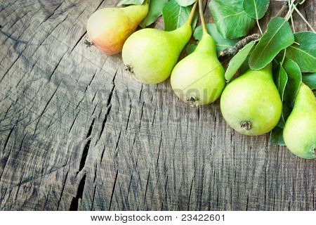 Freshly harvested pears on old wooden background