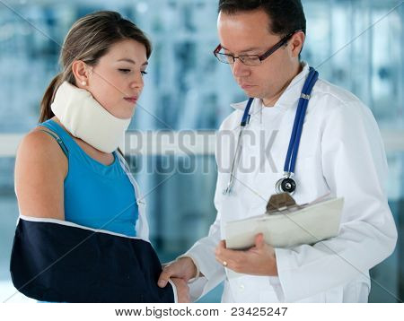 Injured woman in pain at the doctor with a surgical collar and a broken arm