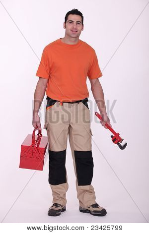 Worker holding a pipe wrench and toolbox