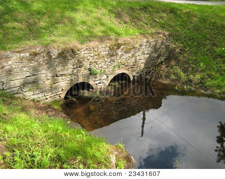 The ancient bridge over silent small river