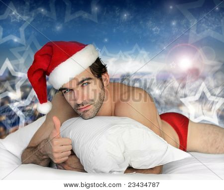 Sexy hunky male model santa laying in bed with magical winter background