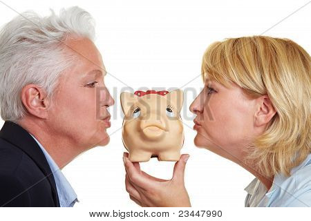 Two Elderly Women Kissing Piggy Bank