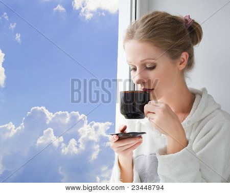 young beautiful woman drinking coffee by the window