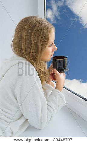 young beautiful girl drinking coffee by the window in the morning