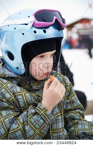 Little Girl In Ski Helmet Eats Sausage