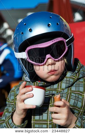 Little Girl In Ski Helmet And Glasses Eats  And Drink