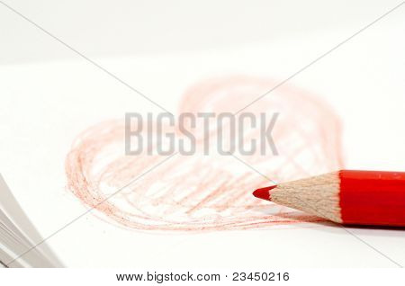 Heart drawn with red crayon on the notebook