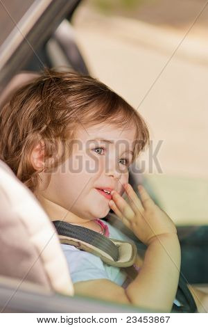 Kid Making Faces Sitting In Car Safety Seat