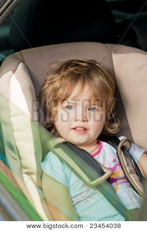 Cute Little Child In Car Safety Seat Smiling