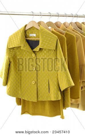Row of designer fashion yellow autumn/winter clothing on hangers