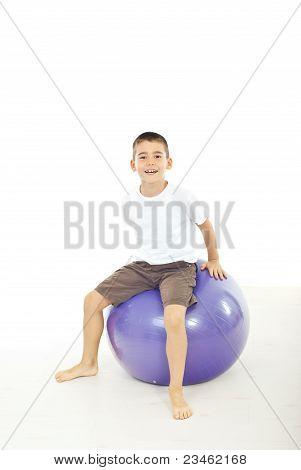 Junge sitzt auf dem großen Ball