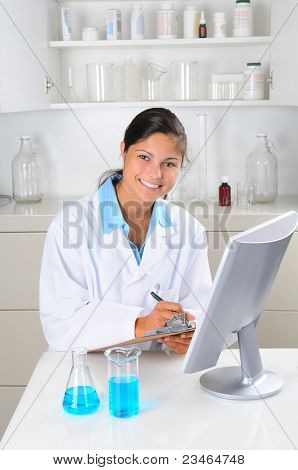 Young female Lab Tech seated behind computer monitor writing notes on a clip board in laboratory setting. Vertical format.