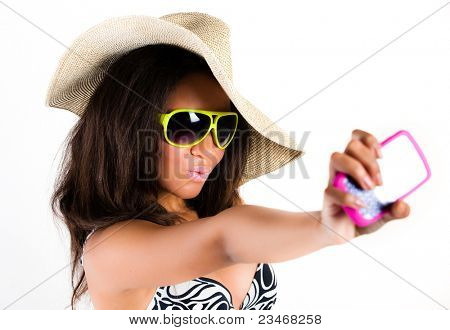 Beautiful young brunette woman in cowboy hat and sunglasses taking a photograph with a mobile cell phone - isolated on white