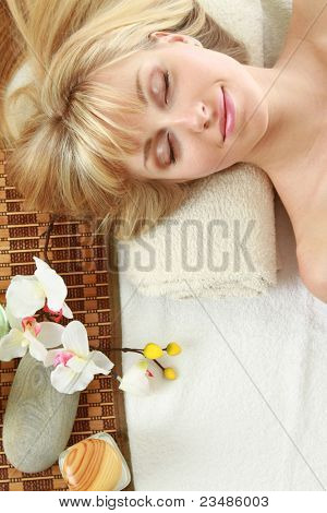 Top view of a relaxed smiling beauty  at spa salon