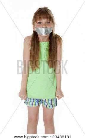 Studio photo of young girl with mouth taped closed, on white background.