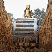 stock photo of land development  - Excavator digging a deep trench - JPG