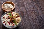 Diet Breakfast Oatmeal Cereal With Kiwi, Banana, Almond And Pomergranate Seeds And Wooden Bowl And S poster