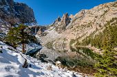 Emerald Lake and reflection with rocks and mountains in snow around at autumn. Rocky Mountain Nation poster