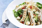 stock photo of caesar salad  - Chicken Caesar salad with romaine lettuce croutons grated parmesan bacon bits and grilled chicken breast - JPG