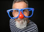 Mature man in funny disguise on dark background. April fools day celebration poster
