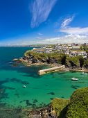 stock photo of verbs  - Cove and harbour of Port Isaac with blue skies - JPG