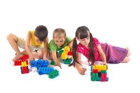 pic of children playing  - Two young boys and a young girl building with multicolor plastic connecting blocks - JPG