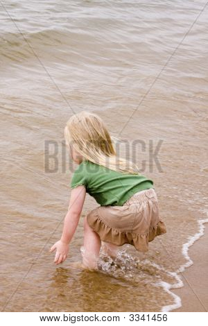 Little Girl Playing At The Beach In The Summer Time